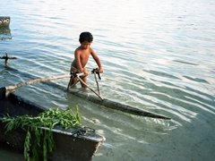Tahitian boy playing with an outrigger canoe; Tiki Village