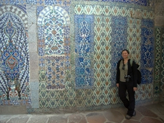 Becky poses next to a magnificent tiled wall; Harem