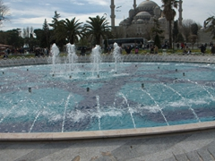 Whirling dervish mosaics on a fountain with Blue Mosque in the background
