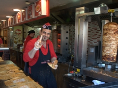 Friendly döner kebap employee beckoning us to try a sample