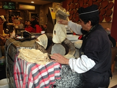 An employee demonstrating how to make thin pita bread at a restaurant on Alemdar Caddesi