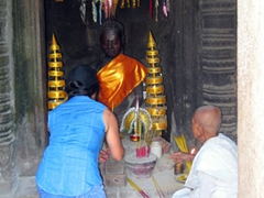 Ann lighting incense at a Buddhist shrine; Angkor Wat