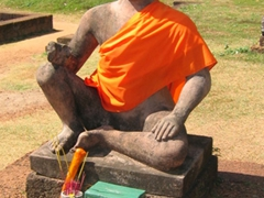 A seated Buddha wrapped in an orange cloth; Angkor Wat