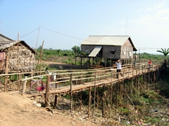 A stilt bridge provides a precarious crossing for these villagers