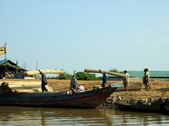 Workers loading bundles of straw onto a boat; Tonle Sap
