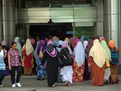 Colorfully clad Muslim women entering the Petronas Towers; Kuala Lumpur