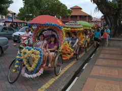 Flower decked rickshaws transport eager tourists around Malacca