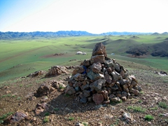 A Mongolian Ovoo (a Shamanism offering to the gods, usually a piramid-shaped pile of rocks which are usually on tops of hills or in mountain passes). When coming across an Ovoo, Mongolians by tradition will walk around the Ovoo three times in clockwise direction and then offer something small