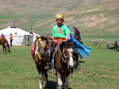 The proud winner of the regional Naadam festival's horse race saunters up to pose for pictures