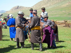 Mongolian men, dressed in traditional attire, in deep conversation following the conclusion of the horse race portion of the Naadam Festival