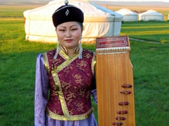 A musician poses beside her Mongolian yatga cither; Karakorum Yurt Camp