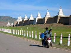 Mongolians on a motorbike (carrying a spare fuel can) stop on the road next to stupas marking the perimeter to Erdene Zuu monastery; Kharkhorin