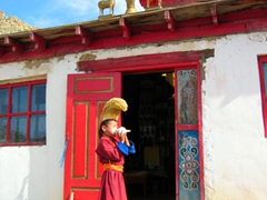 A boy monk blows on a conch shell horn; Erdene Khombo Monastery
