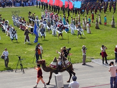 The opening ceremony of the Naadam Festival is an exciting arrangement of colors, sounds, and sights. Here, a lady atop a Bactrian camel plays it up for the crowd