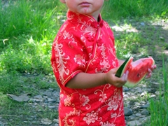 A cute Mongolian girl eats watermelon that matches the color of her dress; Naadam Festival grounds