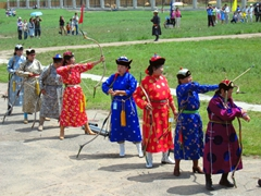 View of female archers dressed in colorful deel and heeled boots; Naadam Festival