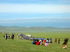 Mongolian police erecting a barrier to keep spectators from inadvertently crossing into the area of the horse race; Naadam Festival