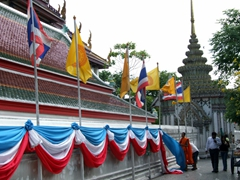 A monk removes cloth decorations from Wat Pho