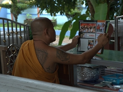 A tattooed monk (not a common sight) reads a magazine; Wat Khunaram on Ko Samui