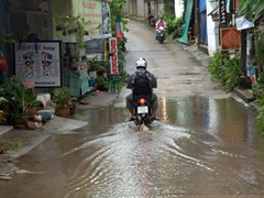 A motorcyclist carefully drives across a puddle in the road (common after a torrential downpour); Ko Samui