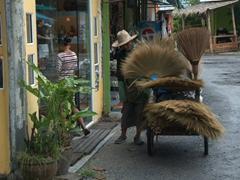 A broom seller conducting door to door business; Ko Samui