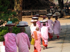 A group of pink robed nuns return to the monastery after receiving donations from locals