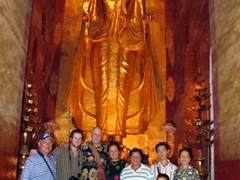 Group photo in front of a 9.5 meter tall Buddha carved from a single piece of teak wood; Ananda Pagoda, Bagan