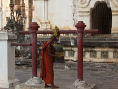 Monk getting ready to ring the bell; Ananda Pagoda