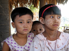Three young children at the toddy farm check us out