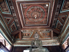 Seated Buddha and decorative carved wood ceiling; Yoke-son Monastery
