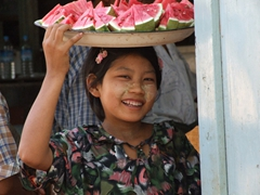 Cute girl selling watermelon shyly smiles for a photo; Salay
