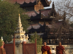 The gorgeous Shwenandaw monastery with two monks strolling in the foreground