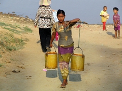 Young woman carries water from the river's edge; Inwa