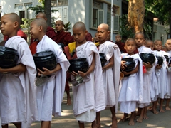 Novice monks (signified by their white robes) lined up with bowls in hand for lunch; Maha Ganayon Kyaung monastery