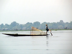 Fisherman paddling his boat with one leg (an Inle Lake tradition)