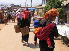 Pa-o ladies strapped with children and baskets exploring Heho market