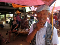 Older man laughs at Bob taking his photograph while smoking a cheroot; Heho market