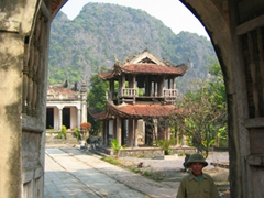An old Vietnamese soldier passing through a temple complex near Tom Coc