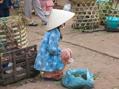 A market vendor looks graceful while patiently squatting, waiting for her next customer