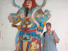 Robby posing beside a statue at Thien Mu Pagoda, Hue