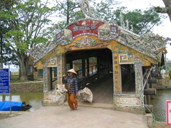 A vendor passes through a covered footbridge in Hue