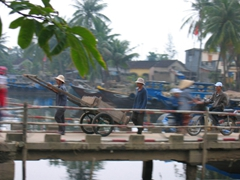 Workers crossing a bridge in Hoi An