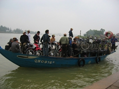 Locals catching a river taxi in Hoi An for mere pennies, as they transport their coveted hondas from one side of the riverbank to the other