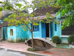 A wooden fishing boat is secured outside the owner's home in quaint Hoi An