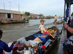 A young boy peddles beer and bananas (what a combo) at the floating market; Can Tho