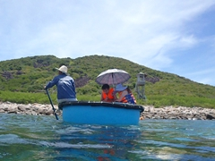 A boatman rows his passengers to shore in a round tub; Nha Trang