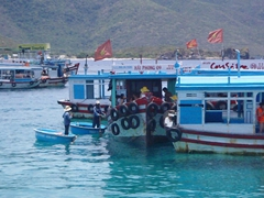 Boatmen offer to ferry passengers to a nearby island for a nominal fee; Nha Trang