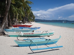 Traditional outrigger boats line the pure white sandy beaches of Boracay