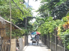An umbrella covered tricycle navigates down a narrow alley; Boracay