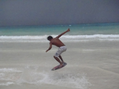 A skim boarding pro shows off his moves; White Beach